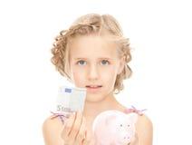 Liten flicka med piggy packar ihop och pengar Royaltyfri Foto