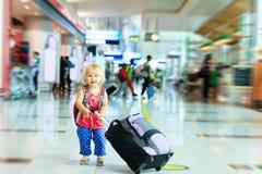 Liten flicka med resväskalopp i flygplatsen arkivfoto