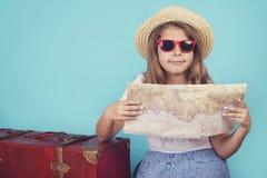 Liten flicka med resväskan och översikten royaltyfria bilder