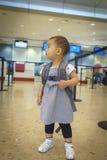 Liten flicka med resväskalopp i flygplatsen Royaltyfri Bild