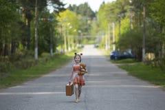 Liten flicka med resväskan som promenerar vägen Gå Arkivfoto
