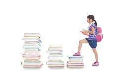 liten flicka med ryggsäcken som går till överkanten av böcker Royaltyfri Bild