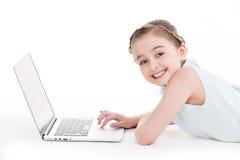 Liten flicka med silverfärgbärbara datorn. Arkivbild