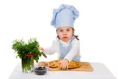 Liten flicka med skäraren och pizza royaltyfria foton
