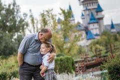 Liten flicka med skolalikformign och hennes farfar i grön medeltal arkivfoton