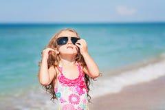 Liten flicka med solglasögon som ser himlen Arkivfoton