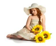 Liten flicka med solrosor Arkivbild