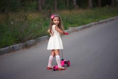 Liten flicka med sparkcykeln på vägen Arkivbilder