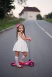 Liten flicka med sparkcykeln på vägen Royaltyfria Bilder