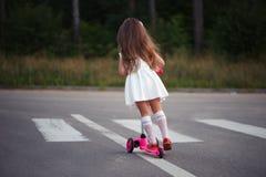 Liten flicka med sparkcykeln på vägen Royaltyfri Foto