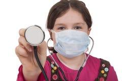 Liten flicka med stetoskopet och kirurgiskt maskerar Arkivbild