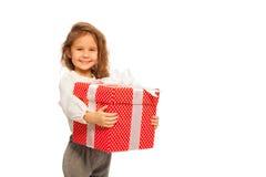 Liten flicka med stor röd gåva på vit arkivbild