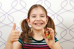 Liten flicka med taco och tummen upp fotografering för bildbyråer
