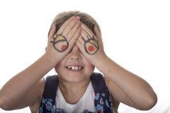 Liten flicka med tecknad filmögon som målas på hennes fåniga händer som gör arkivfoto