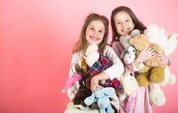 Liten flicka med toyen Två härliga lyckliga flickor som står och omfamnar plushsleksaken i barnrum Mjukhet och royaltyfri fotografi