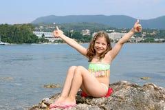 Liten flicka med tummar upp på sommarsemester arkivbild