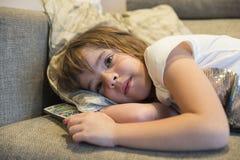 Liten flicka med TVfjärrkontroll Royaltyfria Bilder