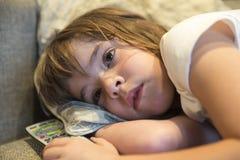 Liten flicka med TVfjärrkontroll Fotografering för Bildbyråer