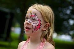 Liten flicka med Unicorn Painted på framsida Royaltyfri Foto