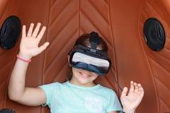 Liten flicka med videospelet för virtuell verklighethörlurar med mikrofonlek Royaltyfri Fotografi