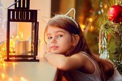 Liten flicka nära en brinnande stearinljus julhelgdagsaftongåvor semestrar många prydnadar Royaltyfria Foton
