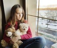 Liten flicka nära fönstret med en nallebjörn arkivbild