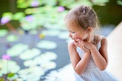 Liten flicka nära liljadamm Arkivbild