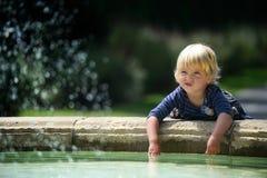 Liten flicka nära springbrunnen Arkivfoto