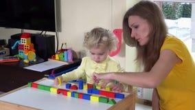 Liten flicka och babysitter som spelar med färgrika träkvarter nära den lilla tabellen arkivfilmer