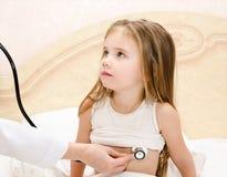 Liten flicka och doktorn för en undersökt undersökning Arkivbilder