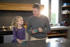 Liten flicka och fader som ser de, medan att äta bär frukt från en bunke Fotografering för Bildbyråer