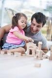 Liten flicka och fader som spelar med träbyggnadskvarter på golv Royaltyfri Bild