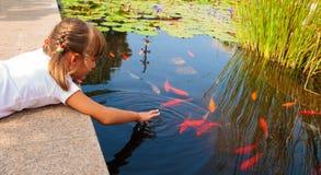Liten flicka och fisk Arkivfoto