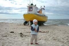 Liten flicka och fiskebåt Arkivbilder