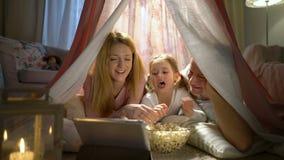 Liten flicka och henne föräldrar som tycker om hålla ögonen på tecknade filmer direktanslutet i tältet i barnkammaren stock video