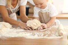 Liten flicka och hennes blonda mamma i beigea förkläden som spelar och skrattar, medan knåda degen i kök hemlagad bakelse royaltyfria foton