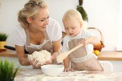 Liten flicka och hennes blonda mamma i beigea förkläden som spelar och skrattar, medan knåda degen i kök hemlagad bakelse royaltyfri fotografi