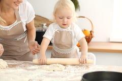 Liten flicka och hennes blonda mamma i beigea förkläden som spelar och skrattar, medan knåda degen i kök hemlagad bakelse royaltyfri bild