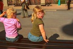Liten flicka och hennes broder som sitter på bänken Lopp runt om Europa Lyckliga roliga familjer royaltyfria foton