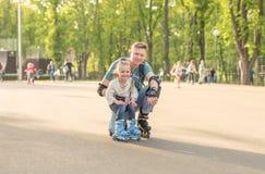 Liten flicka och hennes fader som poserar och åka skridskor för rulle Royaltyfri Foto