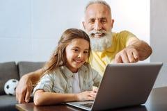 Liten flicka och hennes farfar som håller ögonen på en tecknad film på bärbara datorn Arkivfoto