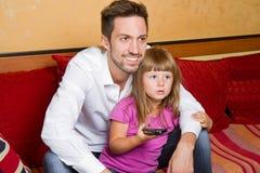 Liten flicka och hennes hållande ögonen på tv för broder Royaltyfri Bild