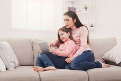 Liten flicka och hennes mamma som hemma använder en minnestavla royaltyfri foto