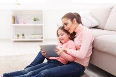 Liten flicka och hennes mamma som hemma använder en minnestavla royaltyfri fotografi