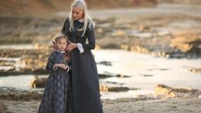 Liten flicka och hennes moder i tappningklänningar av adelsmannar på solnedgången på bakgrunden av havet