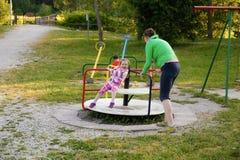 Liten flicka och hennes moder på en lekplats royaltyfri foto