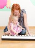 Flickan och hon fostrar att leka pianot royaltyfri bild