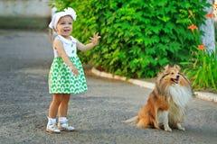Liten flicka och hund som går i parkera Arkivfoton