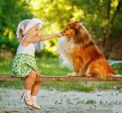Liten flicka- och hundsammanträde på en bänk Royaltyfria Bilder