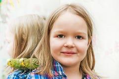 Liten flicka och krabb papegoja Arkivfoton